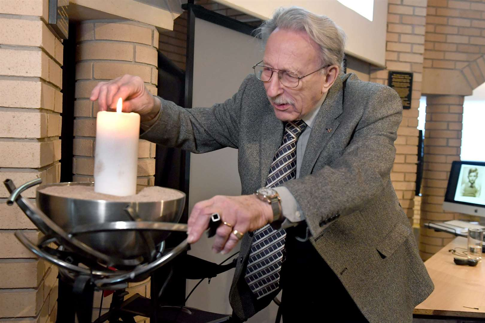 Holocaust survivor Bob Norton lighting a candle at The National Holocaust Centre and Museum. 280120DD4-8