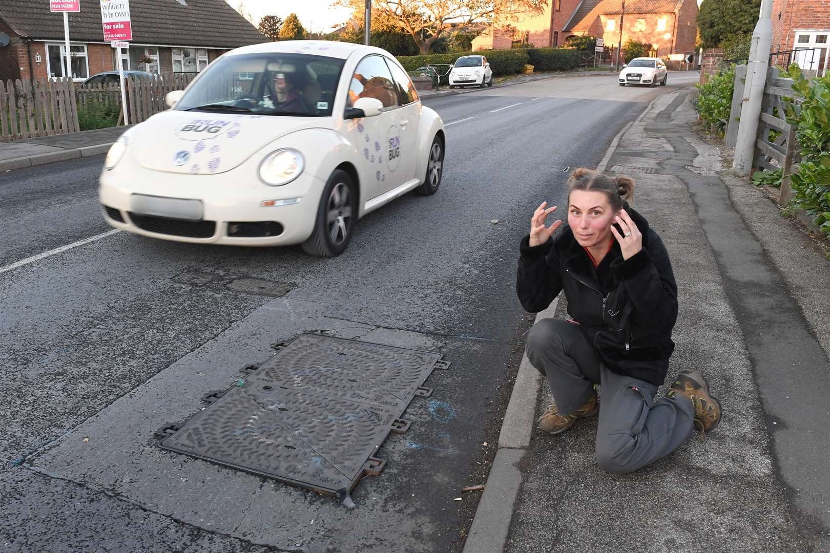 Steel drain cover on the main road through Kirton, bangs everytime a vehicle passes over it, keeping residents awake at night..Resident and member of the Parish Council, Mrs Nicola Batty, next to the drain cover.. (5176596)
