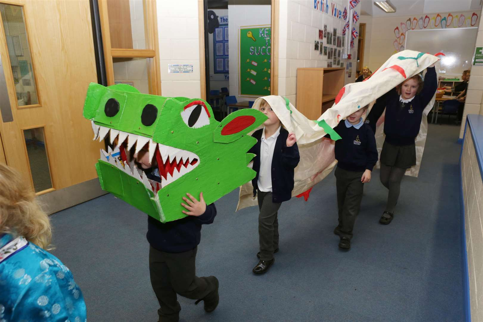 Reception pupils at Claypole School process through neighbouring classrooms spreading good luck as part of their Chinese New Year Celebrations.. (6993334)