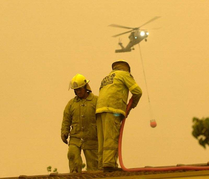 030118...GTidypic...News...DCronin story...Fire storm hits Canberra. At the Emergency Services Bureau at Curtin, firefighters play a hose on the roof of the HQ as a press conference gets underway. A fire bombing helicopter heads off on a mission in the background. (26630165)