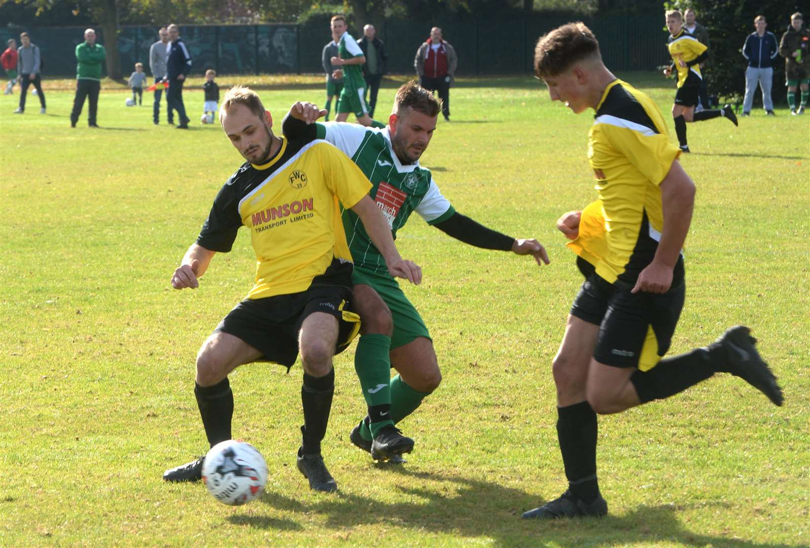 Shane Tetley of Holy Trinity (centre) is muscled off the ball by Rich Willet and Jake Smith (right) of Walesby.. (4688165)