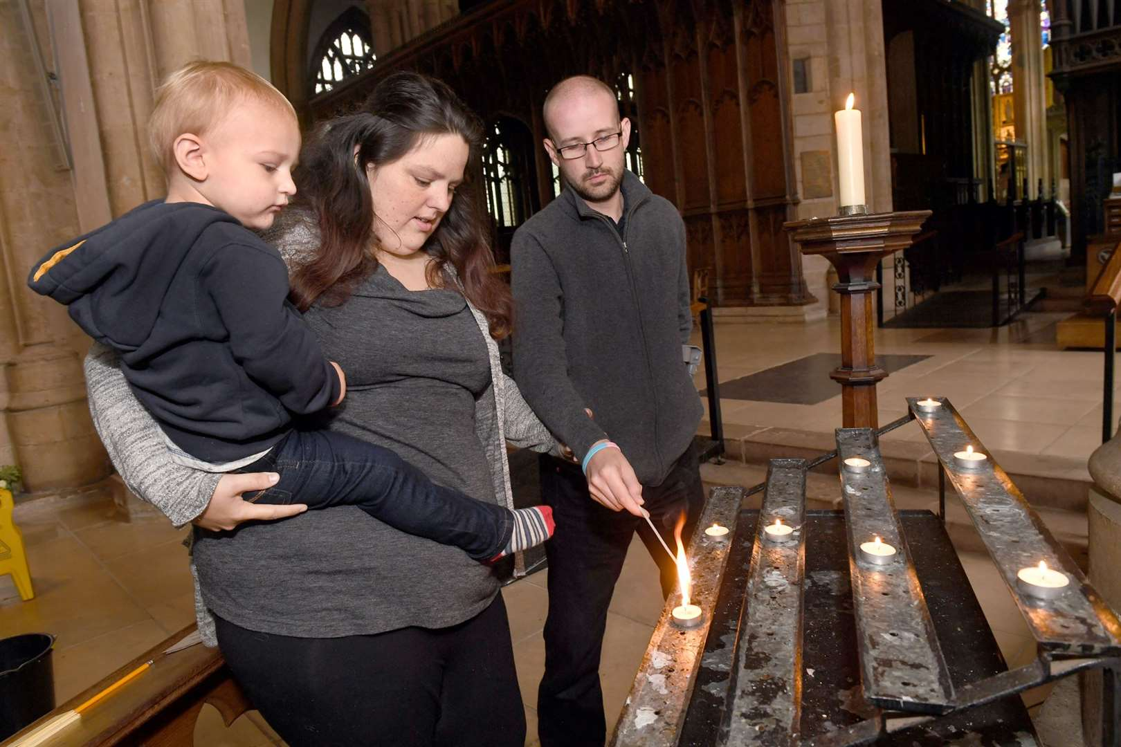 Aimee Scrimshaw and Ben Norfolk who lost their baby at 19 weeks, lighting a candle in Newark Parish Church with their son David-Melvyn Norfolk 2. 011019DD1-6. (18195796)