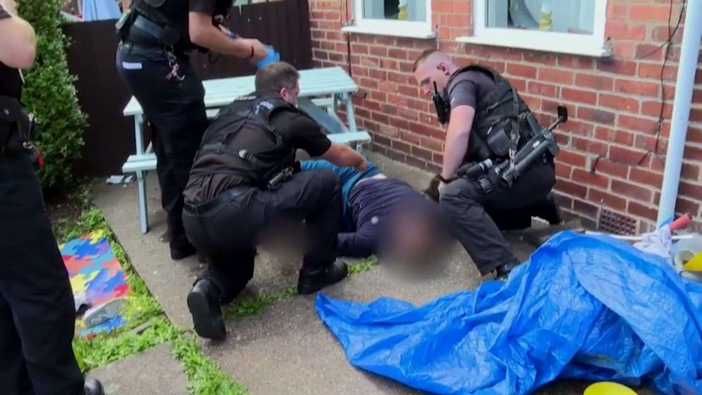 The suspect on the ground surrounded by firearms officers after he fell from the top-floor window of a property. (45700680)