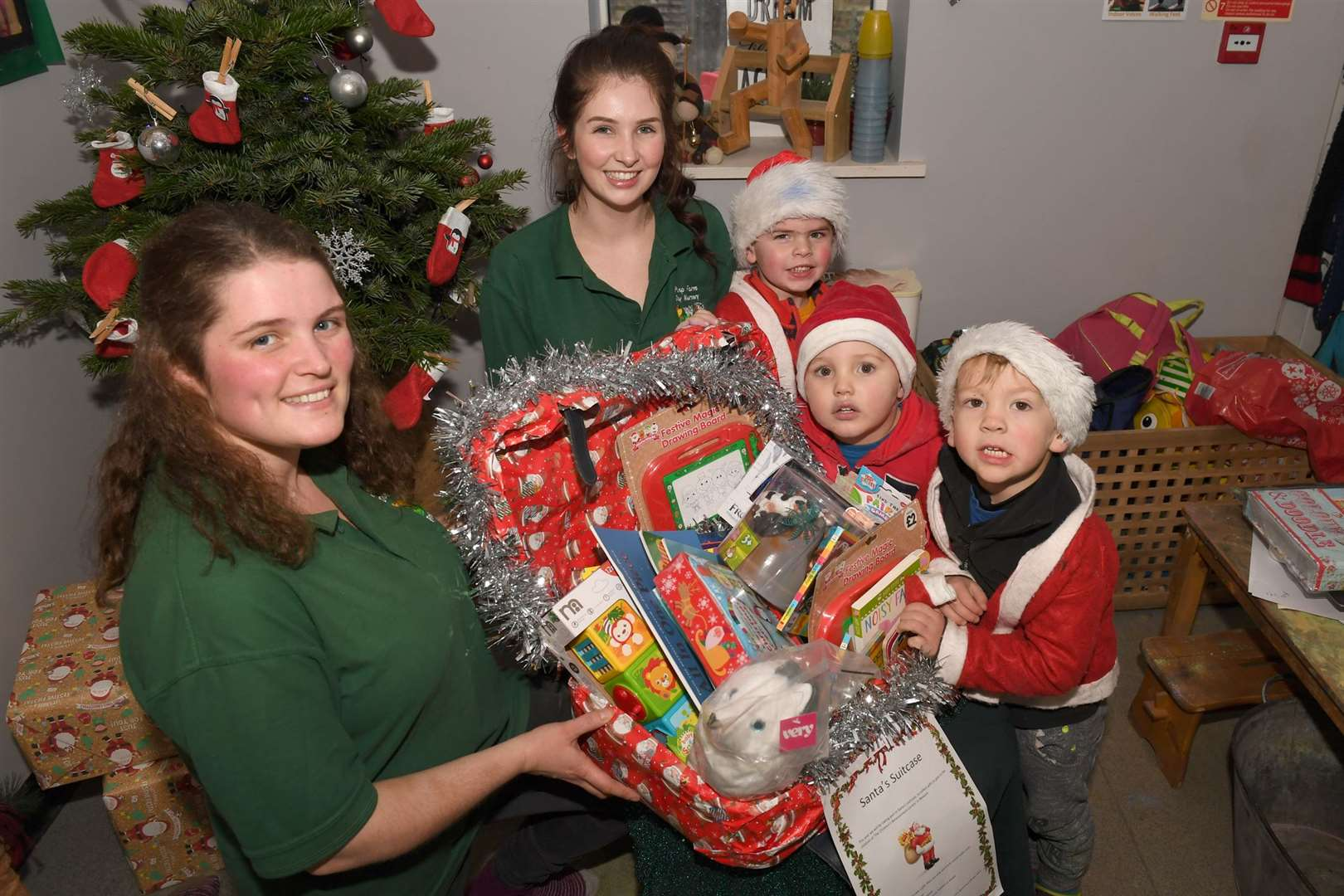 Pump Farm Nursery, Santa's Suitcase initiative. Left to right: Jess Pealing, EYFS coordinator, and Nicole Andrews, deputy manager, pictured with nursery children. 111219DD10-7