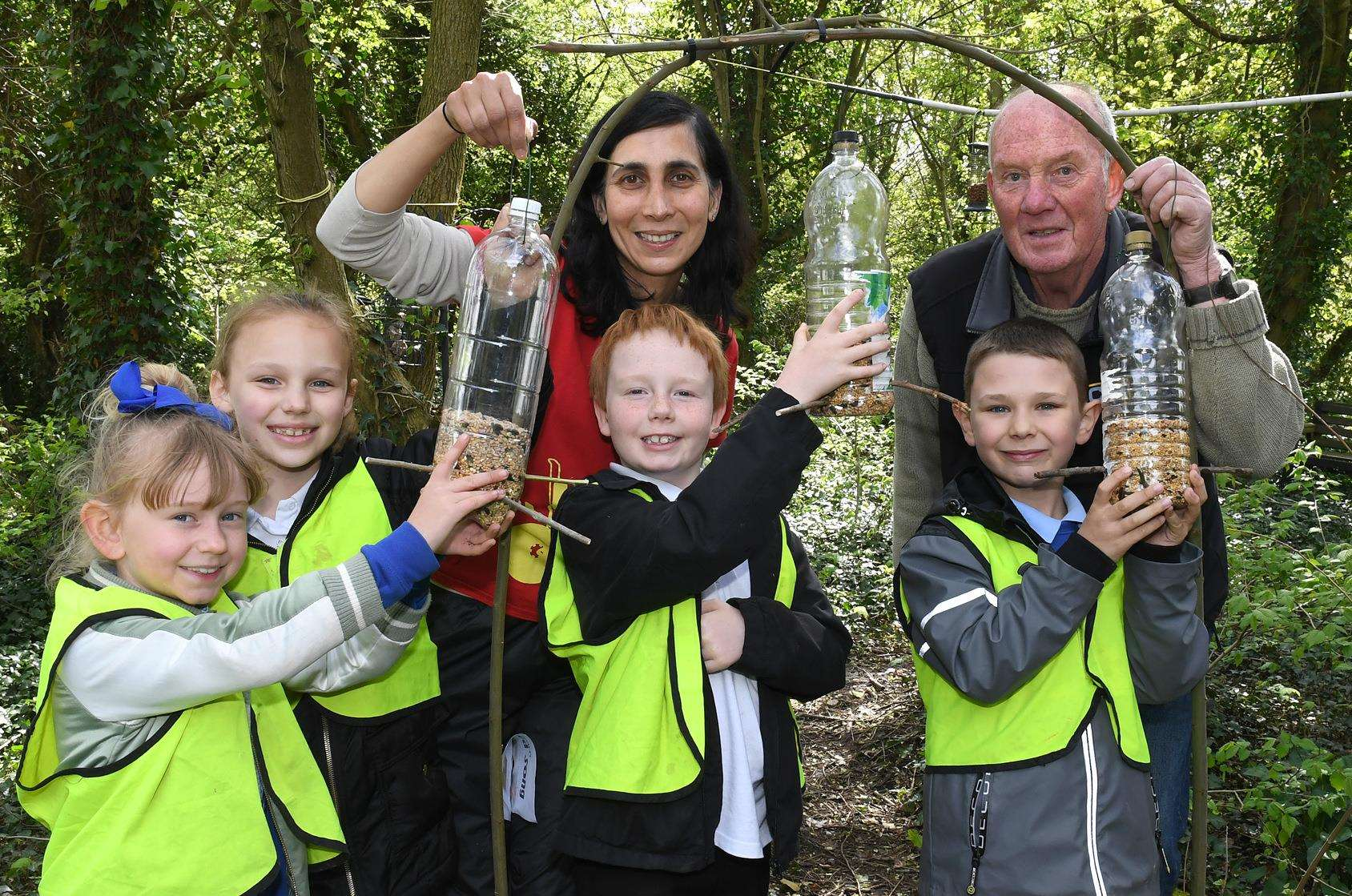 From left, Evie-Mae McRoberts, 7; Megan Fox, 7; Sim Duhra, of Sustrans; Murphy Holland, 8; Mr Roy Fletcher; and Max Lane, 8, hang bird feeders they made. 250418DD6-1